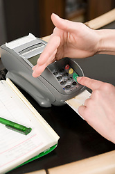 Young woman entering pin in credit card reader
