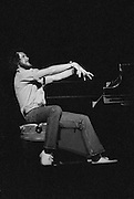 Murray McLaughlin playing piano hands up in drama