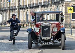 Kerr Wilson (23) from Edinburgh pops a wheelie on his BMX bike past Charlie Brown from Linlithgow in his 1929 classic Austin 16/ EEm