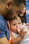 A young father feeding his baby daughter during a family visit in HMP Brixton, South London on the 26th of July 2016, London United Kingdom. The Prisoner Advice & Care Trust (PACT) organise special family days that help the men inside the prison connect with and support their partners and children on the outside. (photo by Andy Aitchison)