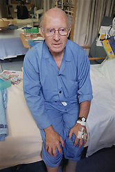 Elderly male patient sitting on hospital bed on ENT ward waiting to be seen by doctor,