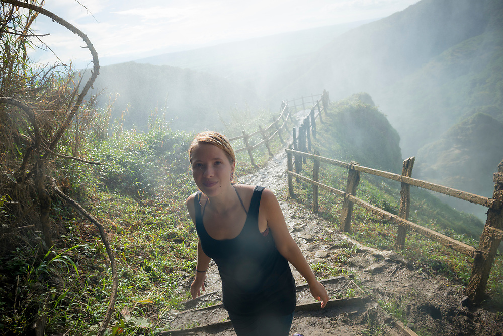 A young woman traveling in Mexico walks away from a lookout point beside the large waterfall (to the right of frame, not pictured) at Cascadas El Chiflón in the southern state of Chiapas, not far from the border with Guatemala. Heavy spray from the waterfall is in the air.