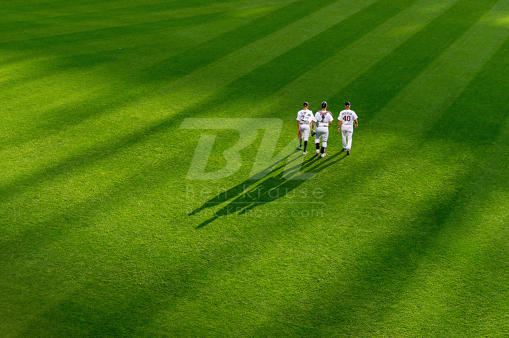 Cole Devries (38), Joe Mauer (7), and Rick Anderson (40).of the Minnesota Twins head for the dugout before a game against the Tampa Bay Rays on August 10, 2012 at Target Field in Minneapolis, Minnesota.  The Rays defeated the Twins 12 to 6.  Photo: Ben Krause
