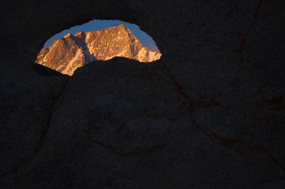 Lone Pine Peak, elevation 12,942 feet, John Muir Wilderness, Inyo National Forest, view through an eroded window in a granite boulder, morning light, April, Alabama Hills Recreation Area, Whitney Portal, eastern Sierra Mountains, Inyo County, California, USA