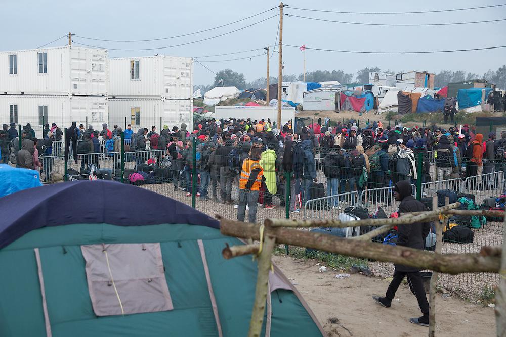 """Calais, Pas-de-Calais, France - 24.10.2016    <br />  <br /> Refugees line up to leave the camp. Start of the eviction on the so called """"Jungle"""" refugee camp on the outskirts of the French city of Calais. Refugees and migrants leaving the camp to get with buses to asylum facilities in the entire country. Many thousands of migrants and refugees are waiting in some cases for years in the port city in the hope of being able to cross the English Channel to Britain. French authorities announced a week ago that they will evict the camp where currently up to up to 10,000 people live.<br /> <br /> <br /> Fluechtlinge stehen in einer Reihe um das Camp zu verlassen. Beginn der Raeumung des so genannte """"Jungle""""-Fluechtlingscamp in der französischen Hafenstadt Calais. Fluechtlinge und Migranten verlassen das Camp um mit Bussen zu unterschiedlichen Asyleinrichtungen gebracht zu werden. Viele tausend Migranten und Fluechtlinge harren teilweise seit Jahren in der Hafenstadt aus in der Hoffnung den Aermelkanal nach Großbritannien ueberqueren zu koennen. Die franzoesischen Behoerden kuendigten vor einigen Wochen an, dass sie das Camp, indem derzeit bis zu bis zu 10.000 Menschen leben raeumen werden. <br /> <br /> Photo: Bjoern Kietzmann"""