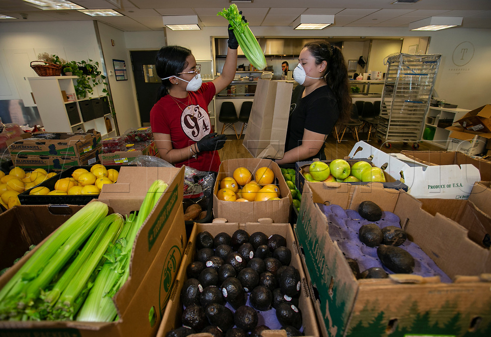 At Three Folds Cafe, Andrea Franco, left, and Ruth Aguilera, at right, package groceries on for customers on Wednesday, March 25, 2020. Due to COVID-19 many restaurants have adjusted their hours and offer expanded services for pick up or delivery and several are turning to selling groceries that would be otherwise stuck up the supply chain at farms, dairies and ranches.