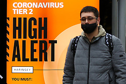 © Licensed to London News Pictures. 13/12/2020. London, UK. A man wearing a face covering walks past the 'Coronavirus Tier 2 High Alert' COIVD-19 public information campaign digital poster in north London amid fears of London going into Tier 3 lockdown restrictions, as the coronavirus infection rate in London is the highest, in England. Photo credit: Dinendra Haria/LNP