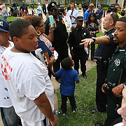A police officer instructs demonstrators of the rules in the protest area, prior to the trial of George Zimmerman at the Seminole County Courthouse, Saturday, July 13, 2013, in Sanford, Fla. Zimmerman had been charged for the 2012 shooting death of Trayvon Martin. Zimmerman was found not guilty by a jury of six women. (AP Photo/Alex Menendez)
