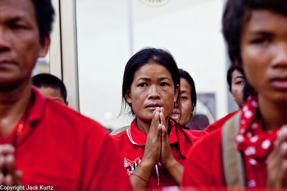 Apr. 15, 2010 - BANGKOK, THAILAND:  Red Shirt protestors pray in front of the caskets of the dead during a chanting service at Wat Hualamphong in central Bangkok Thursday for the people who died during anti-government street violence Saturday. Another protestor died today, bringing the civilian death toll to 17. Hundreds of people are still hospitalized and many are in intensive care. Officials expect the death toll to increase through the week as people die of their wounds. A date has not been set for the victims' Buddhist funeral rites, but the chanting services will continue on a daily basis until the dead are cremated . Many people believe a violent government crackdown is less likely now since the violence seems to have shocked many Thais, but it has also galvanized protestors who show no sign of backing down.     Photo By Jack Kurtz