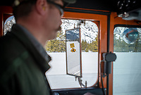 A sign reflected in the plow's rearview mirror shows the snow depth near South Jenny Lake in Grand Teton National Park, currently about three feet.
