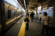 TOKYO, JAPAN, 28 APRIL - ShimoKitaZawa- Man with uniform, helmet, and yellow saftety vest in front of the train with yellow stripe - APRIL 2012 [FR] un homme en uniforme, casque et veste de securite jaune est en face d'un train aux bandes jaunes