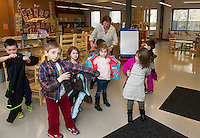 Child Development Center Manager Colleen Bownes helps children with their coats as they head to the outdoors playground area following story time at the Huot Technical Center Daycare on Wednesday afternoon. (Karen Bobotas/for the Laconia Daily Sun)