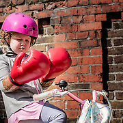A young girl looking bemused as to why she is wearing boxing gloves whilst riding a bike. Shot for a healthcare campaign.