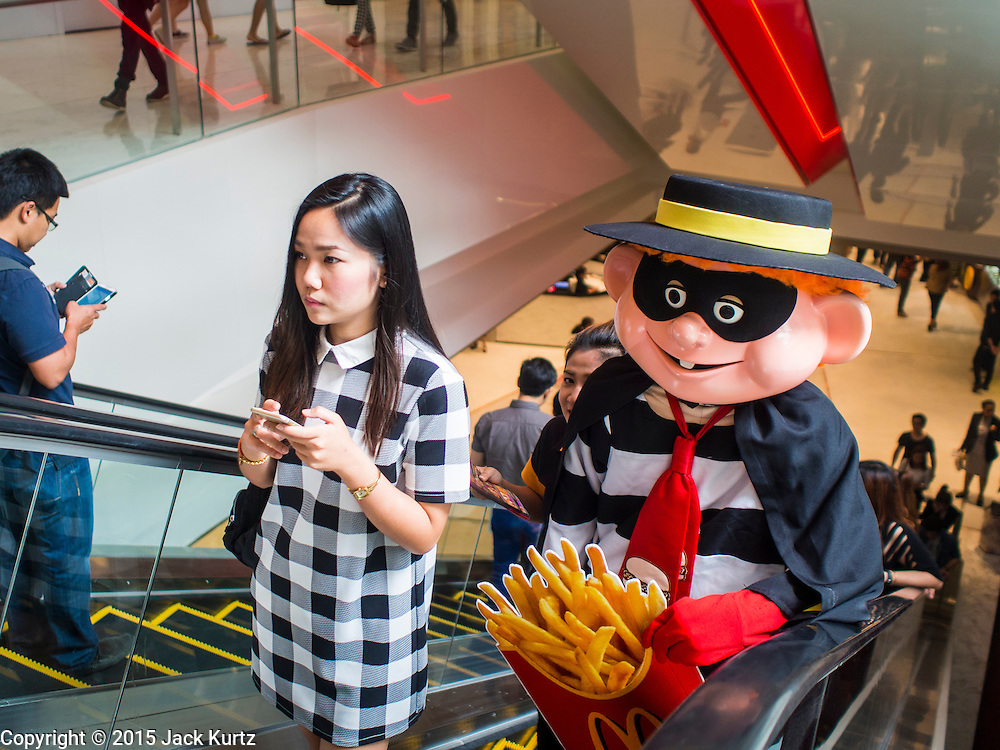 "27 MARCH 2015 - BANGKOK, THAILAND: A woman rides an escalator ahead of the ""Hamburglar,"" a fast food character used to promote McDonald's restaurants in Thailand, in ""EmQuartier,"" a new mall in Bangkok. ""EmQuartier"" is across Sukhumvit Rd from Emporium. Both malls have the same corporate owner, The Mall Group, which reportedly spent 20Billion Thai Baht (about $600 million US) on the new mall and renovating the existing Emporium. EmQuartier and Emporium have about 450,000 square meters of retail, several hotels, numerous restaurants, movie theaters and the largest man made waterfall in Southeast Asia. EmQuartier celebrated its grand opening Friday, March 27.   PHOTO BY JACK KURTZ"