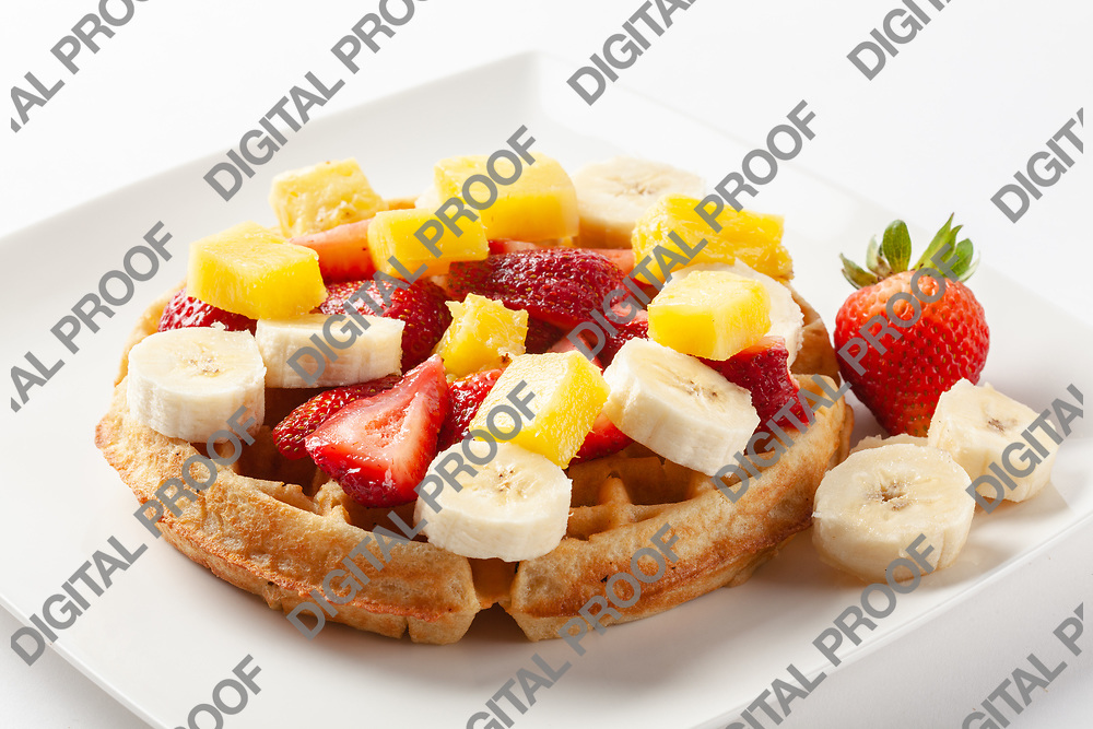 Waffle topped with strawberry, banana and orange fruits isolated in studio with a white background