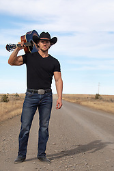 cowboy with a guitar on a rural dirt road