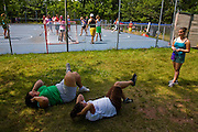 Mackenzie Wolfson plays field hockey with her counterparts who are also part of a weight loss program at Camp Shane in the Catskill Mountains, New York. (MacKenzie Wolfson is featured in the What I Eat: Around the World in 80 Diets.)  A couple other girls do crunches lying on their backs on the grass in the shade on a hot afternoon. There are about 500 male and female campers housed in small cabins on shaded hillsides overlooking athletic fields, a small lake, and the camp's most important building, the cafeteria.