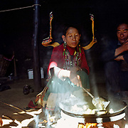 A Yi woman wearing her traditional clothing cooks over an open fire in her kitchen, Ma Long village, Yunnan province, China. The People's Republic of China recognises 55 ethnic minority groups in China in addition to the Han majority. The ethnic minorities form 9.44% of mainland China and Taiwan's total population and the greatest number can be found in Yunnan Province, 34% (25 ethnic groups).