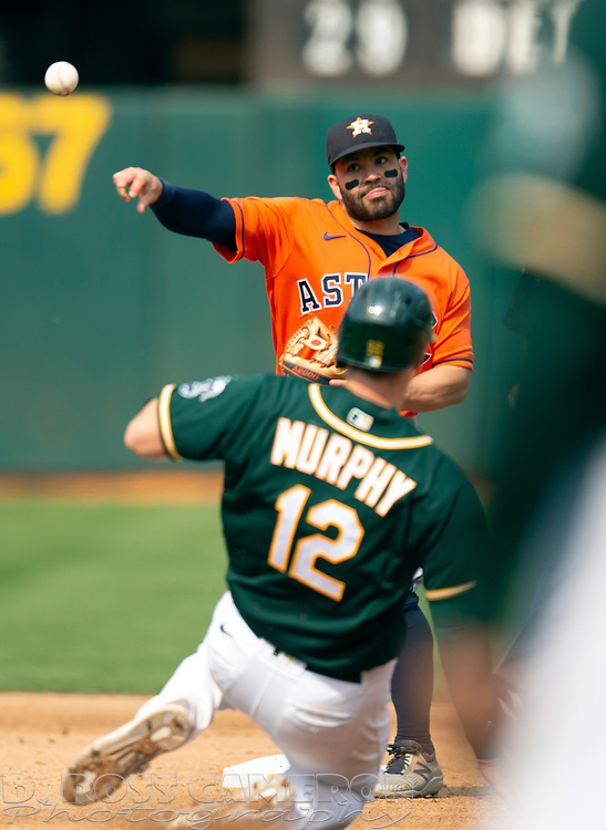 Sep 25, 2021; Oakland, California, USA; Houston Astros second baseman Jose Altuve (27) throws over Oakland Athletics catcher Sean Murphy (12) to complete a double play during the fifth inning at RingCentral Coliseum. Elvis Andrus was out at first base. Mandatory Credit: D. Ross Cameron-USA TODAY Sports