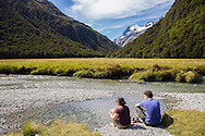 Hikers relaxing by stream on the Routeburn Track, South Island, New Zealand