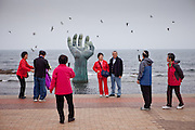 """Visitors photographing each other at the """"Hand of Harmony"""" located at Homigot Beach close to Pohang city at the South Korean East coast."""