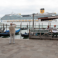 VENICE, ITALY - MAY 06:  A tourist takes a picture of the new flagship of Costa Cruises Fascinosa while she sails in St Mark's Basin during its madien voyage on May 6, 2012 in Venice, Italy. Costa Cruise announced yesterday that new safety systems are installed to avoid tragedies like the one island of Giglio, which saw the Costa Concordia sink with the loss of 34 lives.  (Photo by Marco Secchi/Getty Images)
