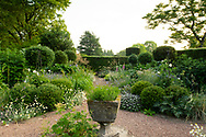 A stone urn surrounded by herbaceous borders and Yew hedge at Cothay Manor, Greenham, Wellington, Somerset, UK