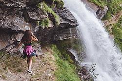 THEMENBILD - eine junge Frau geht auf einem schmalen Wanderweg zum Wasserfall. Das frische Quellwasser ergießt sich über einem großen Felsen, der Wanderweg liegt hinter dem Wasserfall, aufgenommen am 28. Juli 2019 in Fusch a. d. Grossglocknerstrasse, Oesterreich // a young woman walks along a narrow path to the waterfall. The fresh spring water pours over a big rock, the hiking trail lies behind the waterfall in Fusch a. d. Grossglocknerstrasse, Austria on 2019/07/28. EXPA Pictures © 2019, PhotoCredit: EXPA/Stefanie Oberhauser