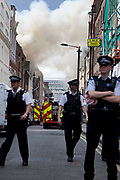 Police cordon off the area. A fire broke out on Dean Streen in Soho, Central London on Friday afternoon. The fire, in a five storey building in the heart of the city raged with firefighters struggling to get the blaze under control. In the nearby streets workers finishing early stood in the smoke filled streets having an end-of-the-week beer in the ghostly atmosphere.