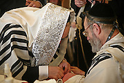On the 8th day after birth a Brit Milah (Circumcision) is performed on a Jewish baby boy (unless there is a medical reason to delay it). The ceremony takes place in the synagogue and the man who carries out the skin removal is know as a Mohel and is medically trained, the boy is also given his Hebrew and/or English names. Here the grandfather of the baby boy assist the Mohel, friends and family attend the ceremony.