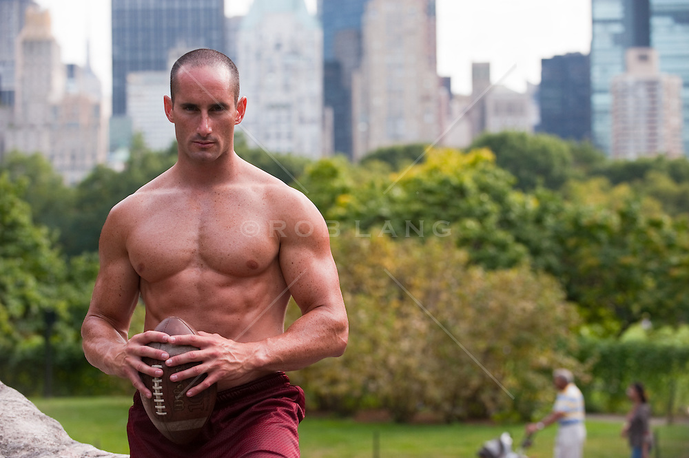 Portraiture of a shirtless muscular young man holding a football in Central Park, New York City