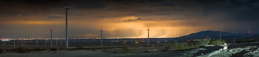 The city lights of Mexicali illuminate a distant storm. As seen from the windmills on the Great Southern Overland Stage Route leading into Ocotillo. Imperial County, CA