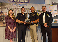 Jennifer Anderson and Charlie St Clair present the 2019 Fritzie Baer Award to Chief Matt Canfield Laconia Police and Chief Mark Armaganian NH State Liquor Commission during the 2019 kickoff for Laconia's 96th Motorcycle Week Rally on Thursday morning at the North East Motor Sports Museum in Loudon.  (Karen Bobotas/for the Laconia Daily Sun)