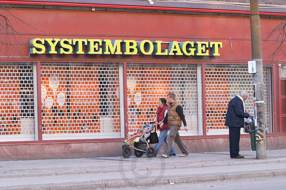The front of one of the Systembolaget shops, the retail monopoly for selling alcohol wine beer and spirits, with a yellow neon sign and the iron wire curtain closed on Soder in the shopping centre Ringen. A man with a plastic bag looking in the rubbish bin for something useful. A young couple with a child in a pram trolley perambulator pushchair buggy stroller walking past looking in the shop window Stockholm, Sweden, Sverige, Europe