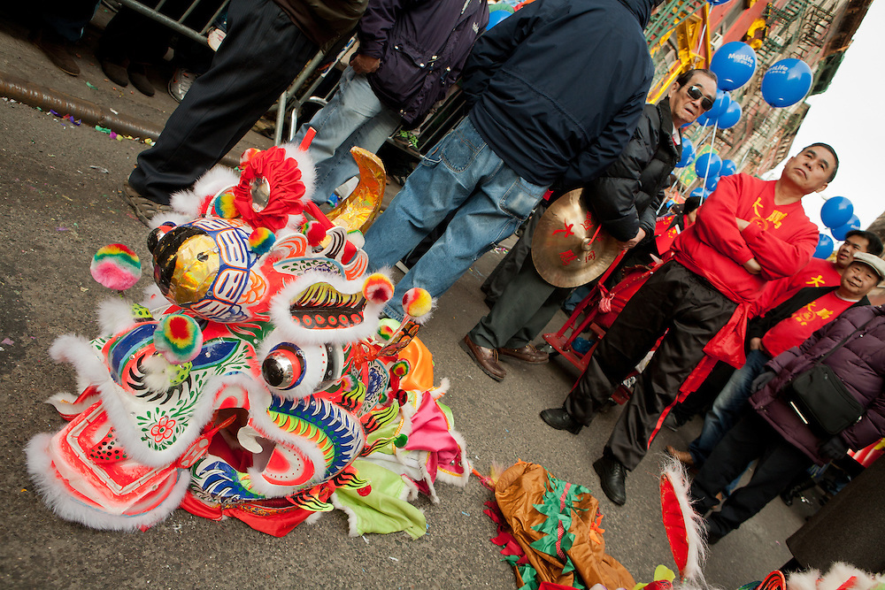 A dragon head on the street. Participants waiting for the parade to start.