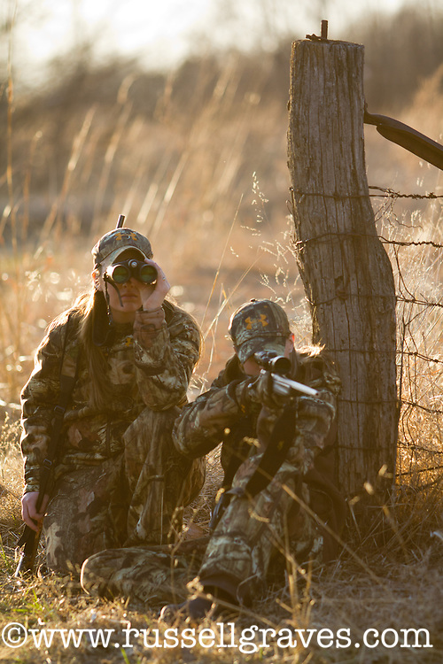 ONE DEER HUNTER SHOOTING WHILE THE OTHER HUNTER WATCHES THROUGH BINOCULARS