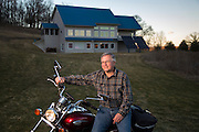 """Victor Zaderej sits on his electric motorcycle out in front of his """"American Passive Home"""" in Oregon, Ill. The 3,200 sq. ft. home titled, Pura Vita, is energy efficient using 80 percent less to heat an cool. Zaderej, an engineer, retrofitted the gas powered motorcycle to electric. (Photo © Andy Manis)"""