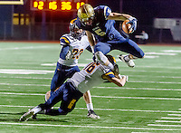 Oak Ridge Trojan Luke Goins (16), tackles Elk Grove Thundering Herd's Gavin Reinwald (5), after his catch and run during the first quarter during the Division 1 Sac-Joaquin Section semi final football game at Elk Grove High School, Friday Nov 27, 2015.<br /> Photo by Brian Baer