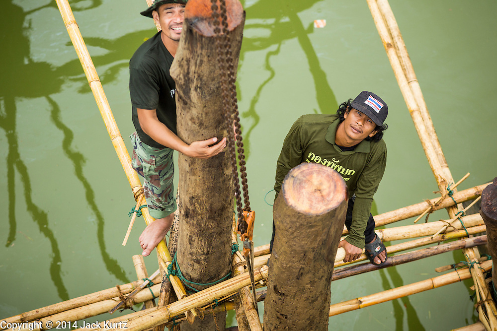 17 SEPTEMBER 2014 - SANGKHLA BURI, KANCHANABURI, THAILAND:  Thai soldiers stand on a piling during repair work on the Mon Bridge. The 2800 foot long (850 meters) Saphan Mon (Mon Bridge) spans the Song Kalia River. It is reportedly second longest wooden bridge in the world. The bridge was severely damaged during heavy rainfall in July 2013 when its 230 foot middle section  (70 meters) collapsed during flooding. Officially known as Uttamanusorn Bridge, the bridge has been used by people in Sangkhla Buri (also known as Sangkhlaburi) for 20 years. The bridge was was conceived by Luang Pho Uttama, the late abbot of of Wat Wang Wiwekaram, and was built by hand by Mon refugees from Myanmar (then Burma). The wooden bridge is one of the leading tourist attractions in Kanchanaburi province. The loss of the bridge has hurt the economy of the Mon community opposite Sangkhla Buri. The repair has taken far longer than expected. Thai Prime Minister General Prayuth Chan-ocha ordered an engineer unit of the Royal Thai Army to help the local Mon population repair the bridge. Local people said they hope the bridge is repaired by the end November, which is when the tourist season starts.    PHOTO BY JACK KURTZ