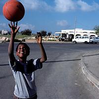 Israel, Kiryat Arba, Portrait of young Falasha boy spinning basketball at West Bank Settlement