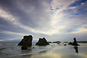 An approaching storm lights up the sky above the sea stacks at Bandon By The Sea, located on the Oregon coast.