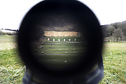 Looking down a firing range towards numbered targets, seen down the telescopic sight of the new British-made Long Range L115A3 sniper rifle on Salisbury Plain, Warminster, England. Sniping means concealment, observation and assassination, a strategy the British are using more against the Taliban in Afghanistan. Swiss Lapua .338 inch rounds (8.59mm) travel at sub-sonic speeds of 936 metres/sec, finding its target accurately up to 1,100 metres. The rifle weighs 6.8kg with telescopic image-intensified scopes to 25x life size vision, made by Schmidt & Bender. Front-mounted 'suppressor' minimises the signature normally compromising snipers' position. At £23,000 each, a £4 million contract has been awarded to Accuracy International, to provide the Army, Royal Marines and RAF. The British say this is the best sniper rifle in the world.