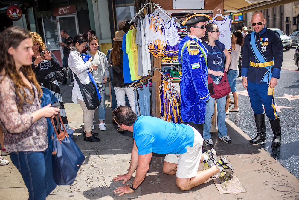 Hollywood, California - April 10, 2015: A man strikes a common pose in front of the TCL Chinese Theatre, kneeling on all fours, matching his hands with a celebrity's handprint. What's not very common on the Hollywood Walk of fame are the Micronationalists, clad in full regalia touring the famous tinsel town strip. Pictured are The Republic of Molossia Commodore Jonathan Miller, his wife Katie Miller, both from Indiana and Grand Duke Travis of WestArctica, and CalSahara.<br /> <br /> <br /> Several MicroCon 2015 attendees toured the Hollywood Walk of Stars. <br /> <br /> MicroCon 2015 is a Micronation conference.<br /> CREDIT: Matt Roth