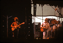 Jerry Garcia and Bob Weir performing with The Grateful Dead Live at Dillon Stadium, Hartford, CT 31 July 1974. Featuring the Wall of Sound. As sun sets behing the stage and the lights came on. Summer weekday show, one of the longest ever played by The Dead.