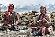 A Rupshu nomad woman twirls prayer beads while another makes yarn from sheep's wool in Thukje, near Tso Kar lake, on Ladakh's Changtang plateau