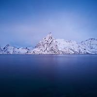 Olstind mountain peak rises from Kjerkfjord in winter, Lofoten islands, Norway