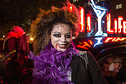 New York, NY, October 31, 2013. A woman in purple boa, with bloodied cheeks in the Greenwich Village Halloween Parade.