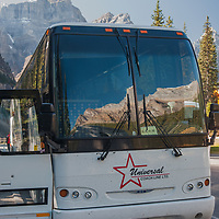 Mountains above The Valley of the Ten Peaks reflect in a tour bus window near Moraine Lake in Banff National Park, Alberta, Canada.