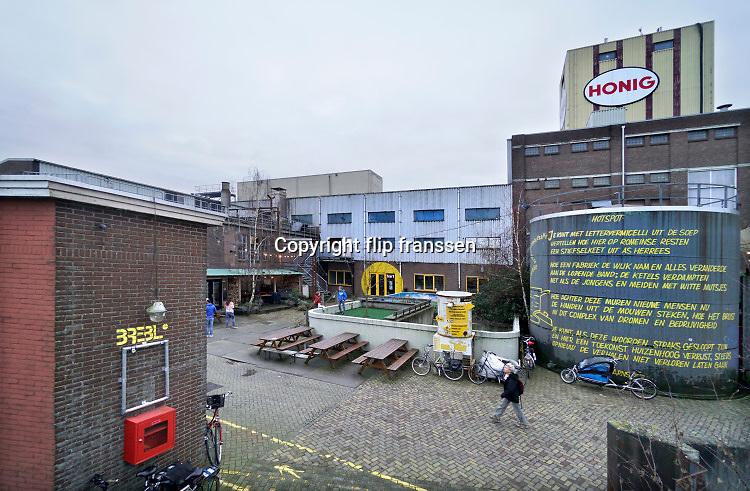 Nederland, Nijmegen, 5-1-2020 Het vroegere fabriekscomplex van de Honig fabriek. Het Honigcomplex is een tijdelijk bedrijfsverzamelgebouw gevestigd in de voormalige Honigfabriek in Nijmegen. Het gebouw huisvest 150 culturele en ambachtelijke bedrijfjes. Het complex met de beeldbepalende meelsilo en het bekende logo staat op de nominatie om in 2022 te worden gesloopt ten behoeve van woningbouw. Het oudste deel en de silo worden behouden . . De gemeente wilde het fabrieksterrein gebruiken voor woningbouw, nieuwbouw woningen. Door de kredietcrisis en de crisis op de woningmarkt is dit plan in 2012 uitgesteld en is het voor een aantal jaren aangewezen als een broedplaats en smeltkroes voor culturele en creatieve activiteiten en ondernemingen waaronder galerie Bart, muziekcafe Brebl . Ook horeca zoals restaurant de Meesterproef en bierbrouwer Oersoep . Foto: Flip Franssen