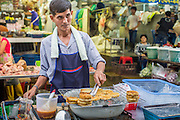 "03 OCTOBER 2012 - BANGKOK, THAILAND:     A snack vendor grills rice cakes in Khlong Toey Market in Bangkok. Khlong Toey (also called Khlong Toei) Market is one of the largest ""wet markets"" in Thailand. Thousands of people shop in the sprawling market for fresh fruits and vegetables as well meat, fish and poultry every day.     PHOTO BY JACK KURTZ"